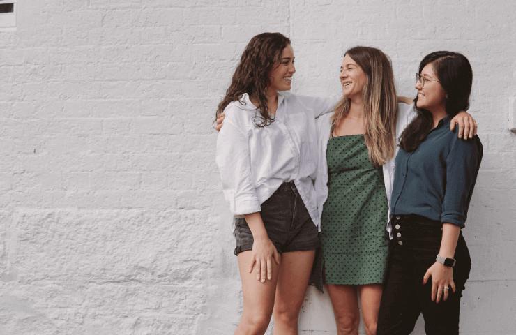 3人で肩を組む女性